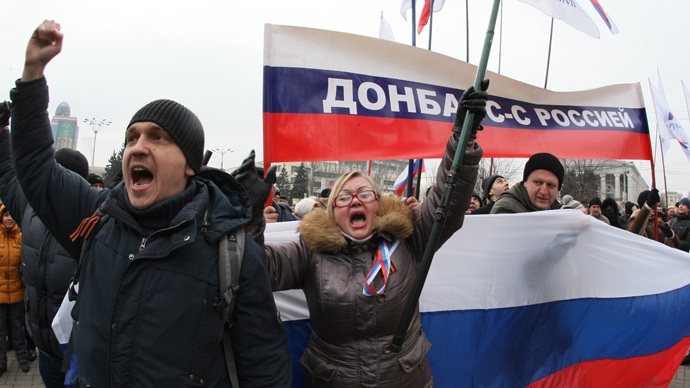 "Pro-Russian protesters wave Russian flags and hold a banner reading ""Donetsk region is with Russia"" during a rally in the industrial Ukrainian city of Donetsk on March 1, 2014 (AFP Photo / Alexander Khudoteply)"