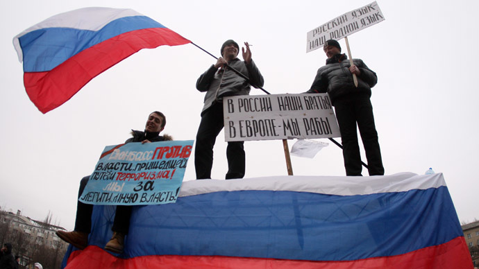 "Pro-Russian protesters wave a Russian flag and hold a sign (C) reading ""Our brothers are in Russia, we are slaves in Europe"" during a rally in front of the regional administration building in the industrial Ukrainian city of Donetsk on March 1, 2014. (AFP Photo)"