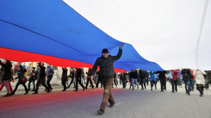 Pro-Russian activists hold a giant Russian flag as they rally in Simferopol, the administrative center of Crimea, on March 1, 2014. (AFP Photo / Genya Savilov)