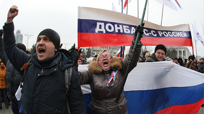 """Pro-Russian protesters wave Russian flags and hold a banner reading """"Donetsk region is with Russia"""" during a rally in the industrial Ukrainian city of Donetsk on March 1, 2014. (AFP Photo / Alexander Khudoteply)"""