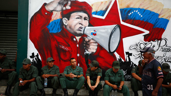 Venezuelan soldiers sit under a mural of late president Hugo Chavez as they attend an event to commemorate the 25th anniversary of the social uprising known as 'Caracazo', which Chavez said marked the start of his revolution, in Caracas February 27, 2014.(Reuters / Jorge Silva)