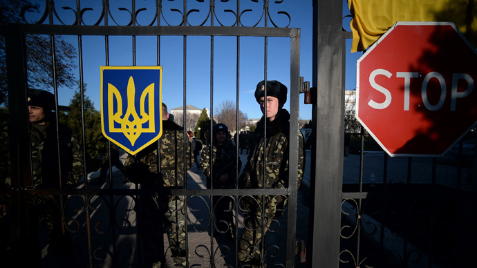 "Ukrainian soldiers look out through a gate near a ""stop"" sign as they wait inside the Sevastopol tactical military brigade base near Belbek in Sevastopol on March 3, 2014 (AFP Photo / Philippo Monteforte)"