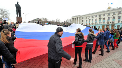 Pro-Russian activists wave a giant Russian flag near a statue of Lenin as they rally in Simferopol, the administrative center of Crimea, on March 1, 2014. (AFP Photo/Genya Savilov)