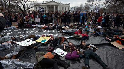 Students protesting against the proposed Keystone XL pipeline lie on a black plastic tarp representing an oil spill in front of the White House in Washington,DC on March 2, 2014. (AFP Photo/Nicholas Kamm)