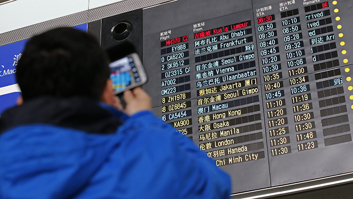 A man takes pictures of a flight information board displaying the Scheduled Time of Arrival (STA) of Malaysia Airlines flight MH370 (top, in red) at the Beijing Capital International Airport in Beijing, March 8, 2014. (Reuters / Kim Kyung Hoon)