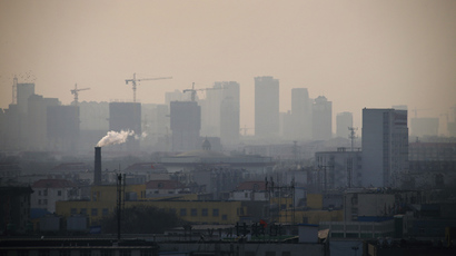 Smoke rises from a chimney among houses as new high-rise residential buildings are seen under construction on a hazy day in the city centre of Tangshan, Hebei province, China (Reuters / Petar Kujundzic)