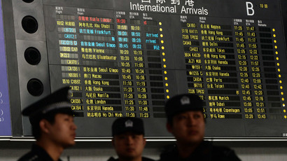 Chinese police stand beside the arrival board showing the flight MH370 (top-red) at the Beijing Airport after news of the Malaysia Airlines Boeing 777-200 plane disapeared on March 8, 2014. (AFP Photo / Mark Ralston)