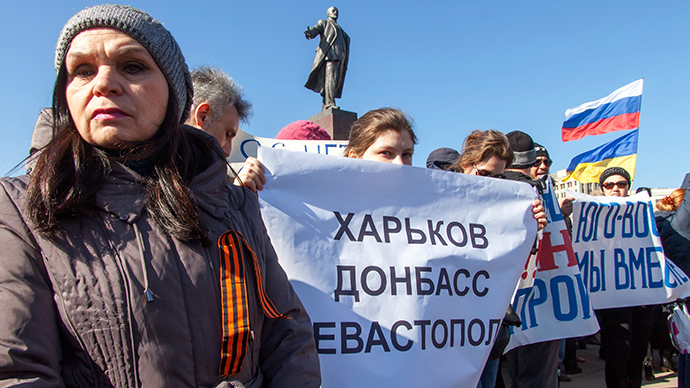 "A girl holds a banner reading ""Kharkiv, Donetsk, Sevastopol"" as pro-Russian supporters attend a rally under the statue of Lenin in the centre of the eastern Ukrainian city of Kharkiv on March 8, 2014 (AFP Photo / Sergey Bobok)"