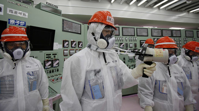 An employee (C) of Tokyo Electric Power Co. (TEPCO) measures using a dosimeter at the central operating control room of the No. 1 and No. 2 reactors at TEPCO's tsunami-crippled Fukushima Daiichi nuclear power plant at Fukushima prefecture March 10, 2014 (Reuters/Koji Sasahara)