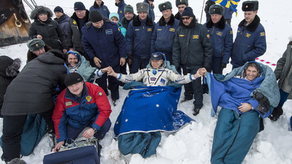 Former ISS commander Oleg Kotov (C) and flight engineers Sergei Ryazansky (L) and Michael Hopkins from NASA sit in chairs outside the Soyuz TMA-10M capsule shortly after they landed in a remote area southeast of the town of Zhezkazgan in central Kazakhstan, March 11, 2014. (Reuters / Bill Ingalls / NASA / Handout via Reuters)