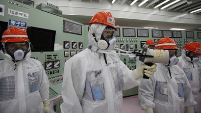 An employee (C) of Tokyo Electric Power Co. (TEPCO) measures using a dosimeter at the central operating control room of the No. 1 and No. 2 reactors at TEPCO's tsunami-crippled Fukushima Daiichi nuclear power plant at Fukushima prefecture March 10, 2014. (Reuters / Koji Sasahara / Pool)