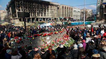 People lay flowers at the barricades in memory of the victims of the recent clashes in central Kiev February 24, 2014. Fugitive Ukrainian President Viktor Yanukovich, ousted after bloody street protests in which demonstrators were shot by police snipers, is wanted for mass murder (Reuters / David Mdzinarishvili)