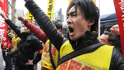 Fukushima nuclear workers and their supporters shouts slogans as they raise their fists in front of the headquarters of Tokyo Electric Power Company (TEPCO), operator of the tsunami-battered Fukushima Daiichi nuclear power plant, during a rally in Tokyo on March 14, 2014. (AFP Photo / Toru Yamanaka)