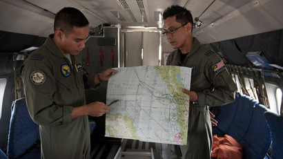 Royal Malaysian Air Force Navigator captain, Izam Fareq Hassan (R) and pilot major Ahmad Shazwan Mohammed (L) show locations on a map during a search and rescue (SAR) operation to find the missing Malaysia Airlines flight MH370 plane over the Strait of Malacca on March 14, 2014. (AFP Photo/Mohd Rasfan)
