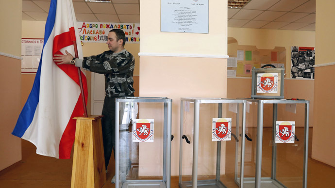 An election commission official installs a Crimean flag during preparations for a referendum at the polling station in Simferopol March 15, 2014. (Reuters/Vasily Fedosenko)