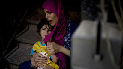 A file photo taken on October 1, 2012 shows a mother holding her wounded daughter as she waits for treatment at the Dar al-Shifa hospital in the northern city of Aleppo (AFP Photo / Zac Baillie)