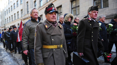 Two man dressed in pre-WWII Latvian military uniforms walk along with veterans of the Latvian Legion, a force that was commanded by the German Nazi Waffen SS, and their sympathizers to the Monument of Freedom in Riga, Latvia on March 16, 2013.(AFP Photo / Ilmars Znotins)