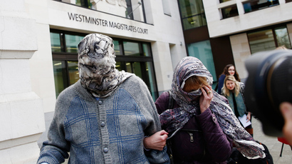 Domenico Rancadore (L) and his wife Anne Skinner cover their faces as they leave after an extradition hearing at Westminster Magistrates Court in central London March 17, 2014 (Reuters / Olivia Harris)