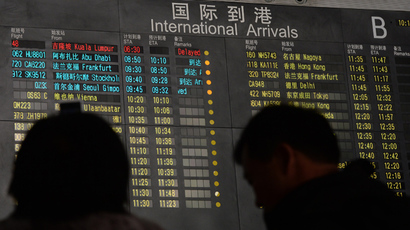 People stand beside the arrival board showing the flight MH370 (top-red) at the Beijing Airport after news of the Malaysia Airlines Boeing 777-200 plane disapeared on March 8, 2014 (AFP Photo / Mark Ralston)