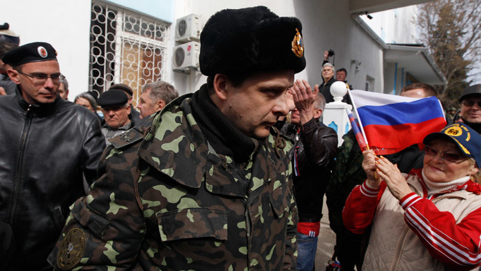 A Ukrainian serviceman (C) passes by pro-Russian supporters and members of self-defence units as he leaves the naval headquarters in Sevastopol, March 19, 2014. (Reuters / Vasily Fedosenko)