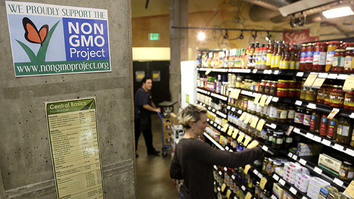 Employees stock shelves near a sign supporting non genetically modified organisms (GMO) (AFP Photo / Jason Redmond)