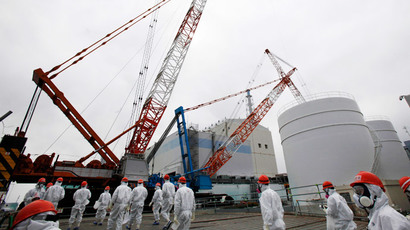 Members of the media and Tokyo Electric Power Co. (TEPCO) employees, wearing protective suits and masks, walk toward the No. 1 reactor building at the tsunami-crippled TEPCO's Fukushima Daiichi nuclear power plant in Fukushima prefecture March 10, 2014.(Reuters / Koji Sasahara)