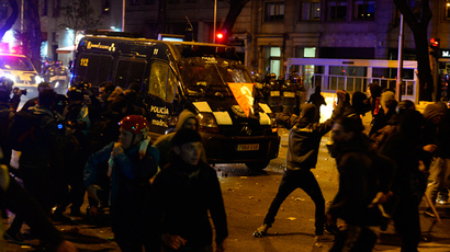 "Demonstrators throw projectiles at a police van during clashes at the end of a march dubbed ""the Marches for Dignity 22-M"" to protest against austerity in Madrid on March 22, 2014 (AFP Photo / Gerard Julien)"