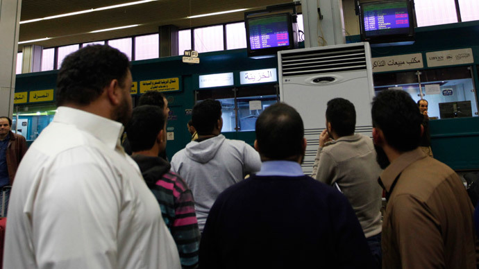 Passengers look at a flight information monitor after the reopening of the airport in Tripoli March 21, 2014. (Reuters / Ismail Zitouny)