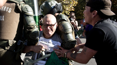 A demonstrator is arrested by riot policeman during a protest to demand free and good quality education and a call for a Constituent Assembly, in Santiago, on March 22, 2014. (AFP Photo / Martin Bernetti)