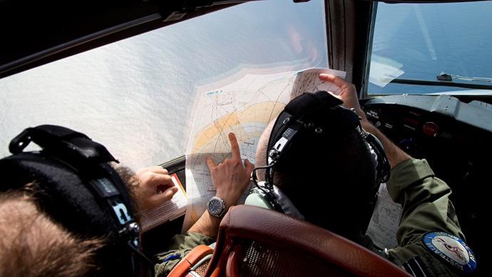 Flight lieutenant Jayson Nichols looks at a map as he flies aboard a Royal Australian Air Force AP-3C Orion aircraft searching for the missing Malaysian Airlines flight MH370 over the southern Indian Ocean on March 27, 2014 (AFP Photo / Pool)