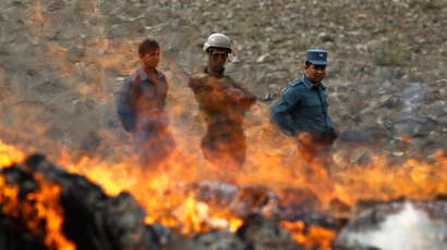 Afghan policemen stand behind a pile of burning narcotics in the outskirts of Kabul (Reuters / Omar Sobhani)