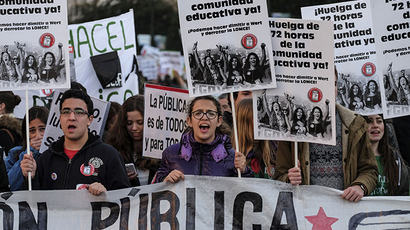 Students hold placards as they demonstrate in the streets of Madrid marking the second day of strikes against the government's cuts in education spending on March 27, 2014. (AFP Photo / Pierre-Philippe Marcou)
