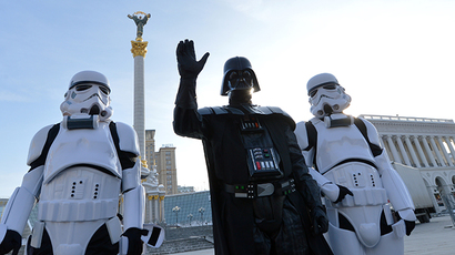 A leader of the Ukrainian Internet Party, wearing a Darth Vader outfit from the Star Wars saga, and other activists, posing as stormtroopers, greet people on December 20, 2012 on Independence Square in Kiev (AFP Photo / Sergey Supinsky)