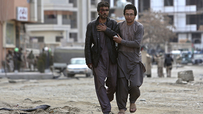 An Afghan man helps an injured man at the site of an attack by Taliban insurgents in Kabul March, 28, 2014. (Reuters / Omar Sobhani)
