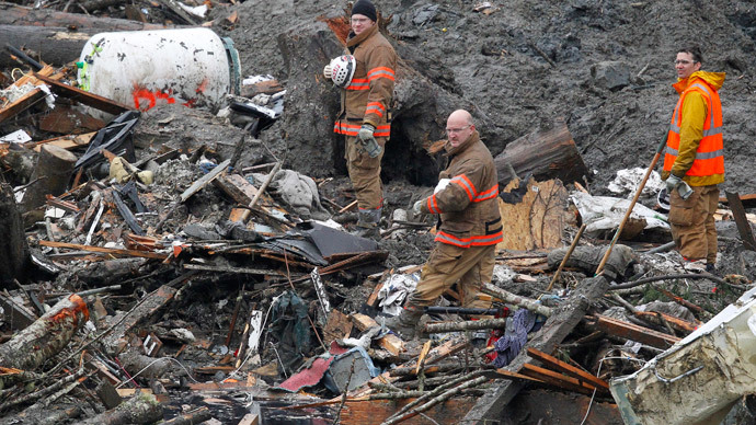 Rescue workers pause for a moment of silence for those lost in the mudslide exactly one week ago in Oso, Washington March 29, 2014.(Reuters / Elaine Thompson)