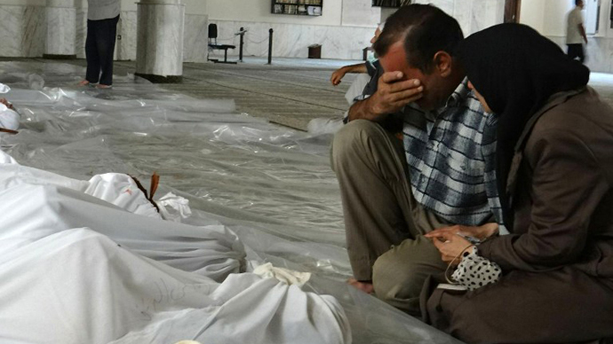 A handout image released by the Syrian opposition's Shaam News Network shows a Syrian couple mourning in front of bodies wrapped in shrouds ahead of funerals following what Syrian rebels claim to be a toxic gas attack by pro-government forces in eastern Ghouta, on the outskirts of Damascus on August 21, 2013. (AFP Photo / Shaam News Network)