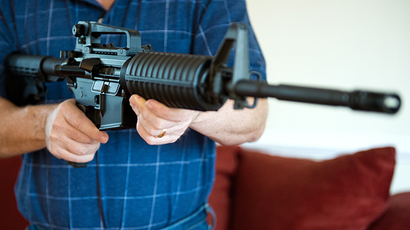 This photo illustration shows a man holding a Colt AR-15 semi-automatic rifle. (AFP Photo / Karen Bleier)