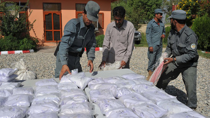 Afghan policemen count bags containing heroin as they are presented to the media at a police station in Jalalabad on September 19, 2013. (AFP Photo / Noorullah Shirzada)