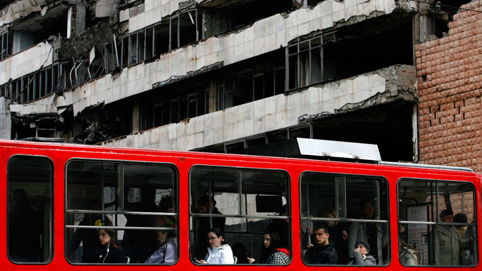 People travel on the tram as they pass a destroyed building of the former federal military headquarters in Belgrade March 24, 2009.(Reuters / Marko Djurica )