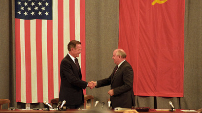 U.S. President George H. W. Bush (L) and Soviet President Mikhail Gorbachev shake hands in front of U.S. and Soviet flags at the end of the press conference in Moscow in this file image from July 31, 1991.(Reuters / Rick Wilking)