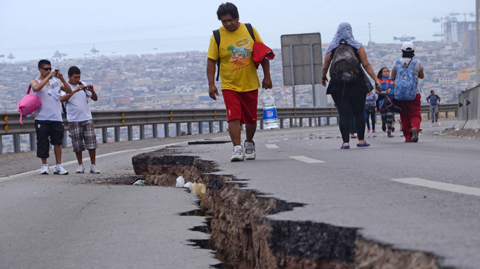 People walk along a cracked road in Iquique, northern Chile, on April 2, 2014 a day after a powerful 8.2-magnitude earthquake hit off Chile's Pacific coast. (AFP Photo / Aldo Solimano)