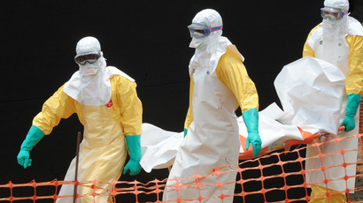 Staff of the 'Doctors without Borders' ('Medecin sans frontieres') medical aid organisation carry the body of a person killed by viral haemorrhagic fever, at a center for victims of the Ebola virus in Guekedou, on April 1, 2014. (AFP Photo)