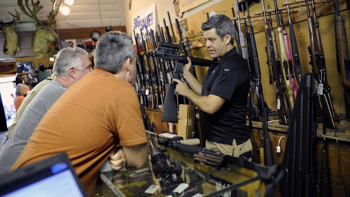 Gun shop owner shows his last two AR-15 style rifles to a group of customers in Sarasota, Florida (Reuters)
