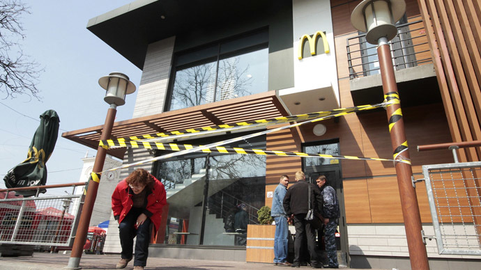 A woman makes her way under a barrier tape outside a McDonald's restaurant, which was earlier closed for clients, in the Crimean city of Simferopol April 4, 2014. (Reuters)