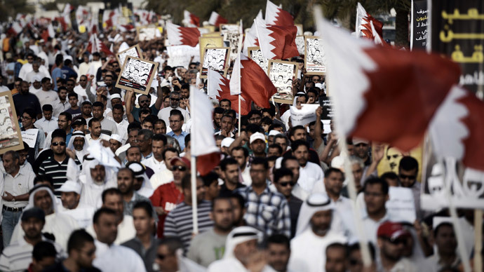 Bahraini hold up the national flag during a demonstration against the Formula One Grand Prix in the village of Shakhurah, west of Manama, on April 4, 2014.(AFP Photo / Mohammed AL-Shaikh)