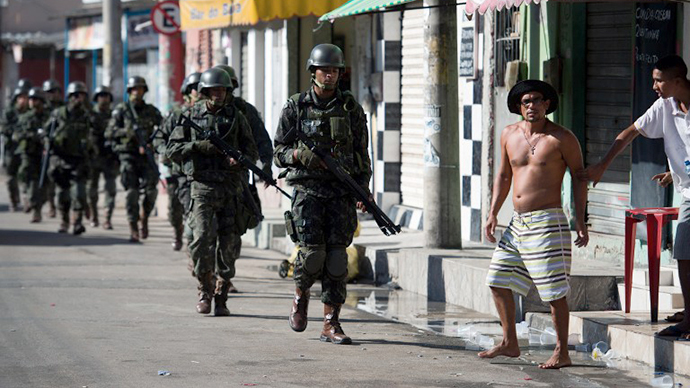 Brazilian soldiers patrol Ramos Favela — part of the Mare shantytown complex near the Galeao (Antonio Carlos Jobim) international airport — in the north suburb of Rio de Janeiro on April 5, 2014. (AFP Photo / Christophe Simon)