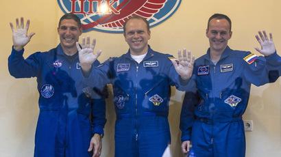 Members of the International Space Station (ISS) crew, (L to R) U.S. astronaut Michael Hopkins, Russian cosmonauts Oleg Kotov and Sergey Ryazanskiy, wave after a news conference behind a glass wall at Baikonur cosmodrome September 24, 2013. (Reuters/Shamil Zhumatov)