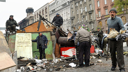 Activists and communal workers dismantle the barricade set on Maidan square during the mass protests of pro-EU opposition against President Viktor Yanukovych regime in  Kiev on April 10, 2014. (AFP Photo / Sergei Supinsky)