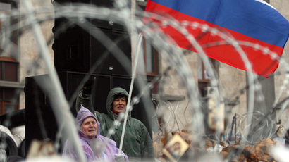 Pro-Russian activists wave a Russian flag and shout slogans during a rally near a razor wire-topped barricade outside the regional government building in the eastern Ukrainian city of Donetsk on April 13, 2014 (AFP Photo / Alexander Khudoteply)