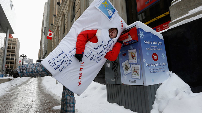 A demonstrator dressed as a mailed envelope jokes around with a mailbox during a protest against planned cuts to Canada Post in Ottawa January 26, 2014. (Reuters / Chris Wattie)